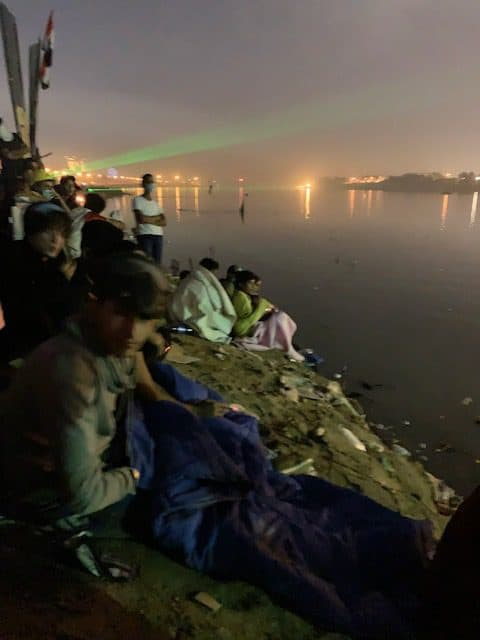 Men are sitting at a river at night