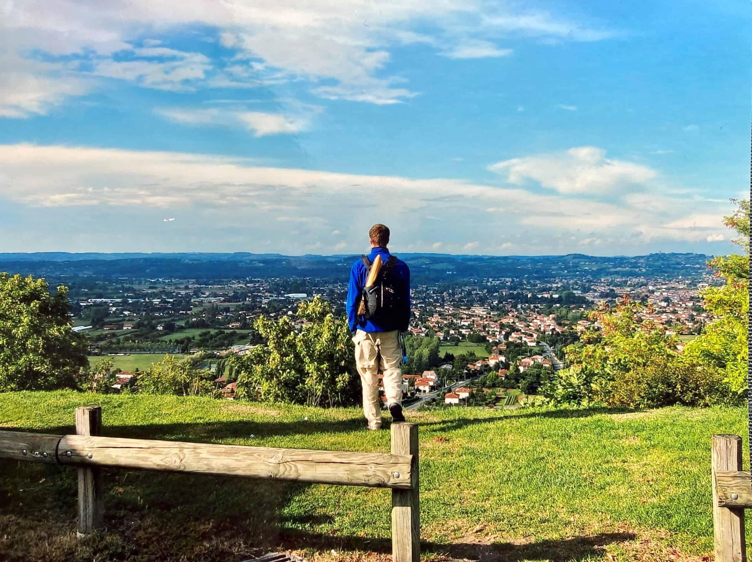 Ein Mann guckt von einem Hügel herunter auf Perigord